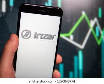 Murcia, Spain; Jan 17, 2019: Hand holding phone with Irizar logo displayed in it with fluctuating graphic on background. First person view