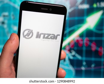 Murcia, Spain; Jan 17, 2019: Irizar logo in phone with earnings graphic on background. Irizar Group is a Spanish-based manufacturer of luxury bus and coach