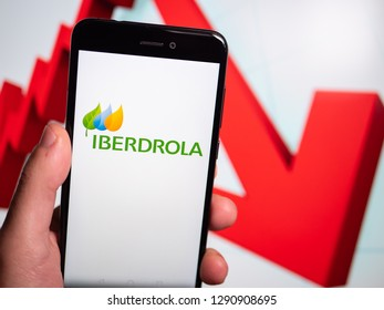 Murcia, Spain; Jan 17, 2019: Iberdrola logo in phone with losses graphic on background. First person view