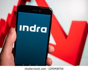 Murcia, Spain; Jan 17, 2019: Indra Sistemas blue logo in phone with losses graphic on background. First person view