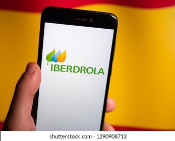 Murcia, Spain; Jan 17, 2019: Iberdrola logo in phone with spanish flag on background. Iberdrola is a Spanish public multinational electric utility company