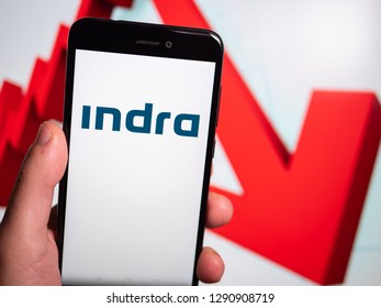 Murcia, Spain; Jan 17, 2019: Indra Sistemas white logo in phone with losses graphic on background. First person view
