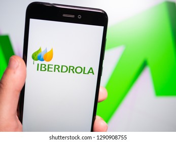 Murcia, Spain; Jan 17, 2019: Iberdrola logo in phone with rises graphic on background. First person view