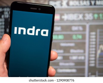 Murcia, Spain; Jan 17, 2019: Indra Sistemas blue logo in phone with stock exchange screen on background. First person view