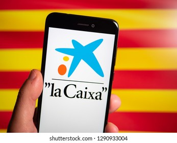 Murcia, Spain; Jan 17, 2019: La Caixa logo in phone with Catalonia flag on background. First person view