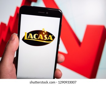Murcia, Spain; Jan 17, 2019: Lacasa logo in phone with losses graphic on background. First person view