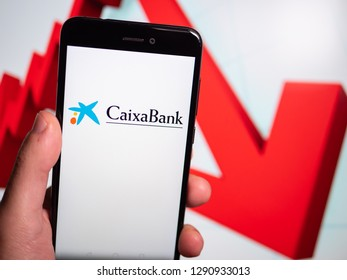 Murcia, Spain; Jan 17, 2019: Caixa Bank logo in phone with losses graphic on background. First person view