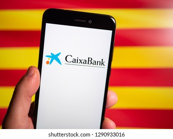 Murcia, Spain; Jan 17, 2019: Caixa Bank logo in phone with Catalonia flag on background. First person view