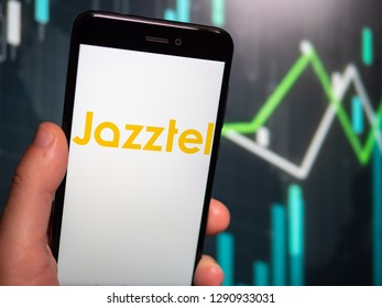 Murcia, Spain; Jan 17, 2019: Hand holding phone with Jazztel logo displayed in it with fluctuating graphic on background. First person view