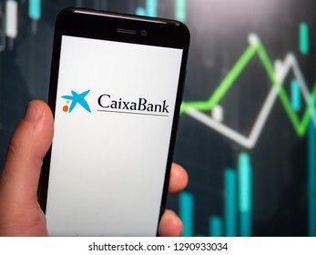 Murcia, Spain; Jan 17, 2019: Hand holding phone with Caixa Bank logo displayed in it with fluctuating graphic on background. First person view