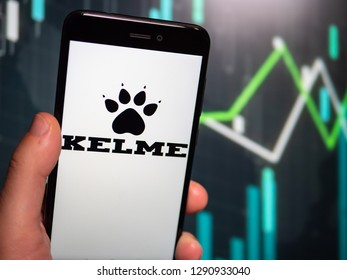 Murcia, Spain; Jan 17, 2019: Hand holding phone with Kelme logo displayed in it with fluctuating graphic on background. First person view