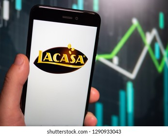 Murcia, Spain; Jan 17, 2019: Hand holding phone with Lacasa logo displayed in it with fluctuating graphic on background. First person view