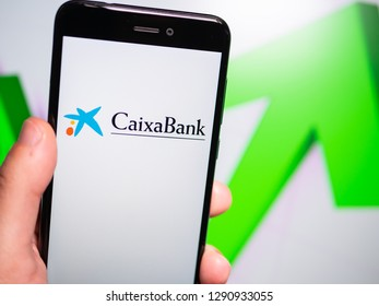 Murcia, Spain; Jan 17, 2019: Caixa Bank logo in phone with rises graphic on background. First person view