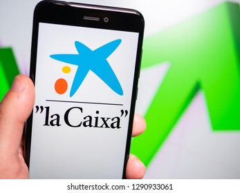 Murcia, Spain; Jan 17, 2019: La Caixa logo in phone with rises graphic on background. First person view