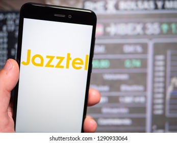 Murcia, Spain; Jan 17, 2019: Jazztel logo in phone with stock exchange screen on background. First person view