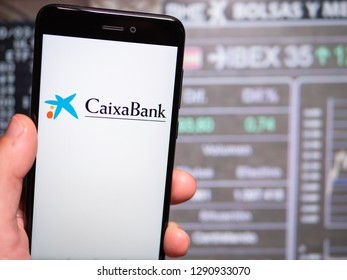 Murcia, Spain; Jan 17, 2019: Caixa Bank logo in phone with stock exchange screen on background. First person view