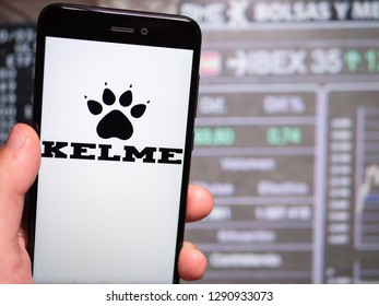 Murcia, Spain; Jan 17, 2019: Kelme logo in phone with stock exchange screen on background. First person view
