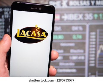 Murcia, Spain; Jan 17, 2019: Lacasa logo in phone with stock exchange screen on background. First person view