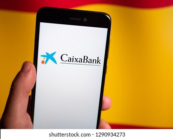 Murcia, Spain; Jan 17, 2019: Caixa Bank logo in phone with spanish flag on background. Caixa Bank is currently Spain's third largest financial institution