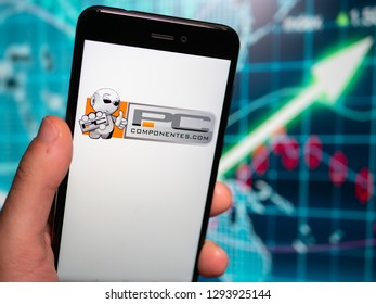 Murcia, Spain; Jan 17, 2019: PcComponentes icon in phone with earnings graphic on background. PcComponentes is a spanish ecommerce of hardware and computers