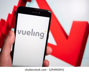 Murcia, Spain; Jan 17, 2019: Vueling Airlines logo in phone with losses graphic on background. First person view