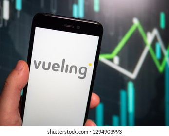 Murcia, Spain; Jan 17, 2019: Hand holding phone with Vueling Airlines logo displayed in it with fluctuating graphic on background. First person view