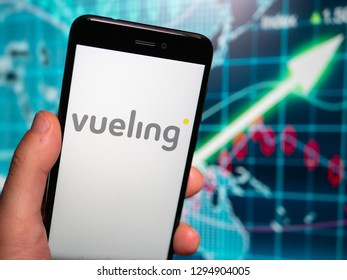 Murcia, Spain; Jan 17, 2019: Vueling Airlines logo in phone with earnings graphic on background. Vueling is a Spanish low-cost airline