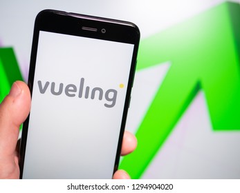 Murcia, Spain; Jan 17, 2019: Vueling Airlines logo in phone with rises graphic on background. First person view