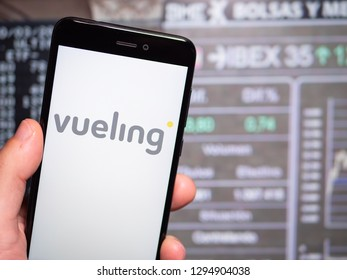 Murcia, Spain; Jan 17, 2019: Vueling Airlines logo in phone with stock exchange screen on background. First person view