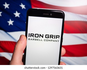 Murcia, Spain; Jan 23, 2019: Iron Grip Barbell Company logo in phone with United States flag on background. Iron Grip Barbell Company is a manufacturer of commercial free weight equipment