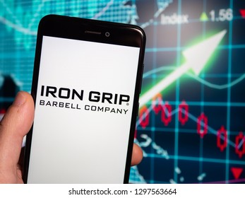 Murcia, Spain; Jan 23, 2019: Iron Grip Barbell Company logo in phone with earnings graphic on background. Iron Grip Barbell Company is a manufacturer of commercial free weight equipment