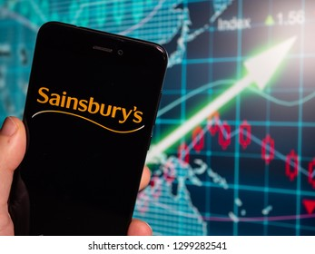 Murcia, Spain; Jan 28, 2019: Sainsbury's black logo in phone with earnings graphic on background. Sainsbury's is the second largest chain of supermarkets in the United Kingdom