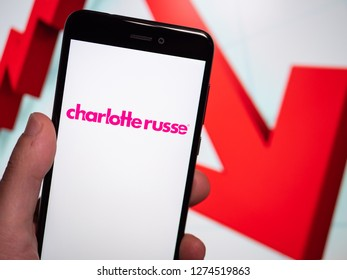 Murcia, Spain; Jan 3, 2019: Charlotte Russe pink logo in phone with losses graphic on background. First person view