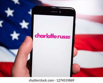 Murcia, Spain; Jan 3, 2019: Charlotte Russe pink logo in phone with United States flag on background. Charlotte Russe is an American clothing retail chain store that operates in the United States