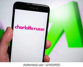 Murcia, Spain; Jan 3, 2019: Charlotte Russe pink logo in phone with rises graphic on background. First person view