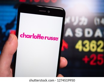 Murcia, Spain; Jan 3, 2019: Charlotte Russe pink logo in phone with stock exchange screen on background. First person view