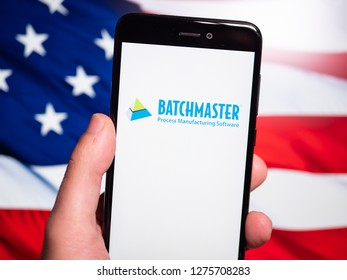Murcia, Spain; Jan 3, 2019: BatchMaster Software logo in phone with United States flag on background. First person view