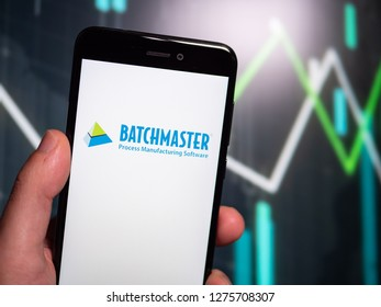 Murcia, Spain; Jan 3, 2019: Hand holding phone with BatchMaster Software logo displayed in it with fluctuating graphic on background. First person view