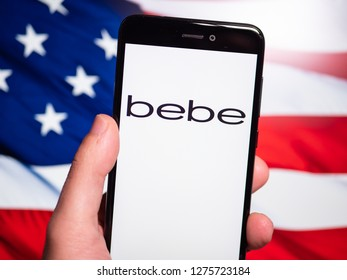 Murcia, Spain; Jan 3, 2019: Bebe Stores logo in phone with United States flag on background. Bebe Stores is a women's retail brand