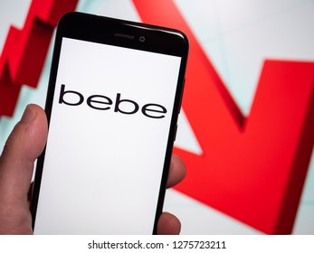 Murcia, Spain; Jan 3, 2019: Bebe Stores logo in phone with losses graphic on background. First person view