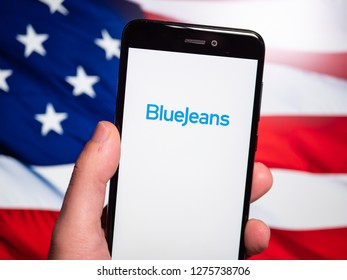 Murcia, Spain; Jan 3, 2019: BlueJeans logo in phone with United States flag on background. BlueJeans Network is a company that provides an interoperable cloud-based video conferencing service