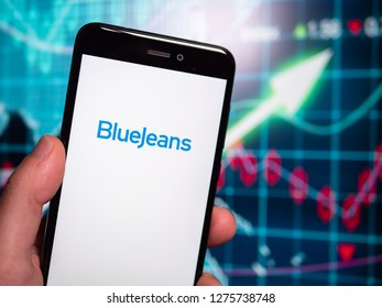 Murcia, Spain; Jan 3, 2019: Bluejeans Network logo in phone with earnings graphic on background. BlueJeans Network is a company that provides an interoperable cloud-based video conferencing service