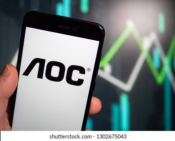 Murcia, Spain; Jan 31, 2019: Hand holding phone with AOC International logo displayed in it with fluctuating graphic on background. First person view