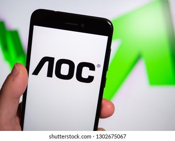 Murcia, Spain; Jan 31, 2019: AOC International logo in phone with rises graphic on background. First person view