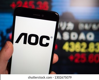 Murcia, Spain; Jan 31, 2019: AOC International logo in phone with stock exchange screen on background. First person view