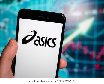Murcia, Spain; Jan 31, 2019: Asics black logo in phone with earnings graphic on background. Asics is a Japanese multinational corporation which produces footwear