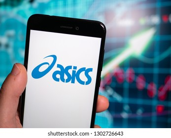 Murcia, Spain; Jan 31, 2019: Asics blue logo in phone with earnings graphic on background. Asics is a Japanese multinational corporation which produces footwear