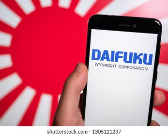 Murcia, Spain; Jan 31, 2019: Daifuku logo in phone with rising sun flag on background. First person view