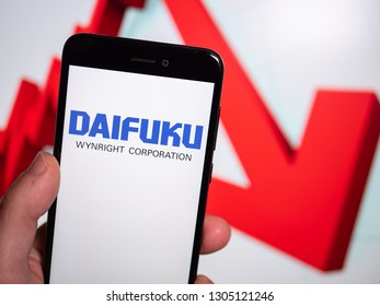 Murcia, Spain; Jan 31, 2019: Daifuku logo in phone with losses graphic on background. First person view