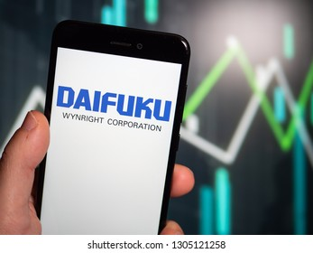 Murcia, Spain; Jan 31, 2019: Hand holding phone with Daifuku logo displayed in it with fluctuating graphic on background. First person view
